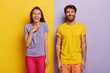 canvas print picture - Photo of two delighted young woman and man stand together, express good emotions, smile happily, spend free time together, have fun, pose against yellow and purple background, dressed casually