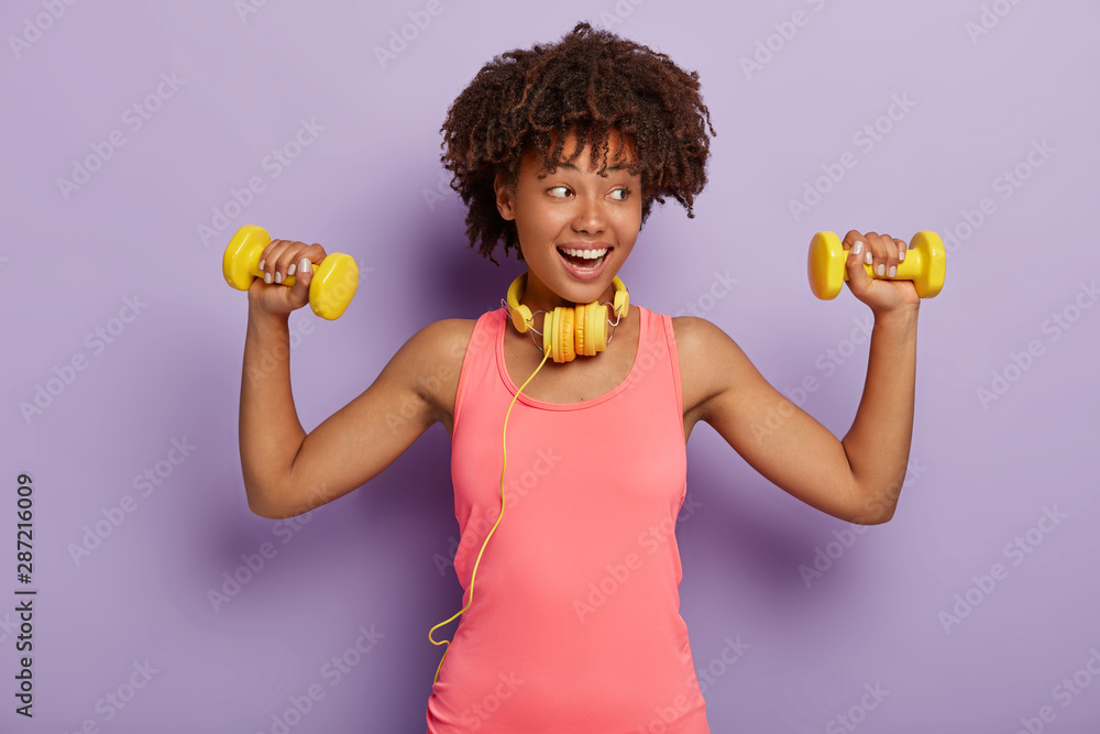 Fototapety, obrazy: Pleased dark skinned model with curly hair, dressed in casual rosy t shirt, raises arms with dumbbells, trains muscles, listens music via headphones, isolated over purple background. People and sport