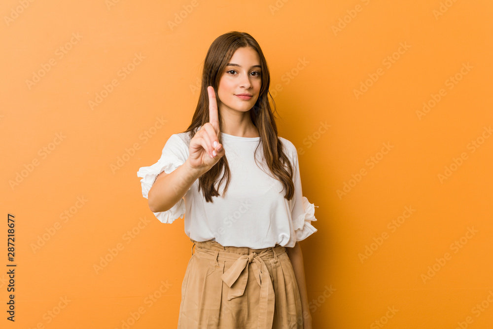 Fototapety, obrazy: Young caucasian woman showing number one with finger.