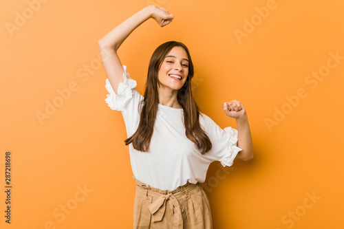 Fotografia  Young caucasian woman celebrating a special day, jumps and raise arms with energy