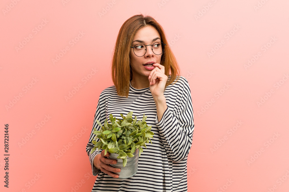 Fototapety, obrazy: Young woman holding a plant relaxed thinking about something looking at a copy space.