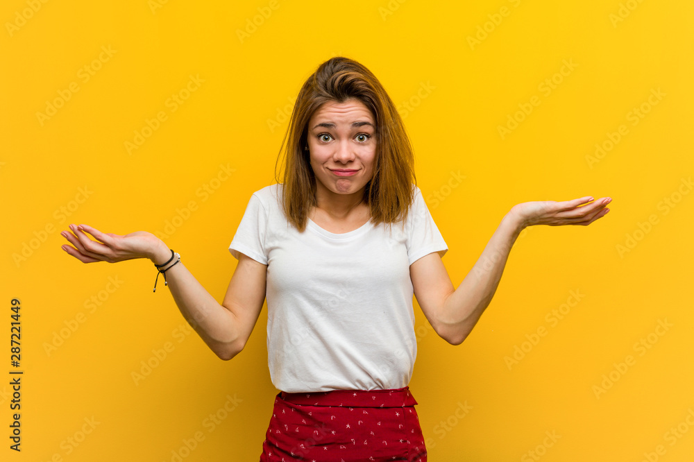 Fototapety, obrazy: Young natural caucasian woman doubting and shrugging her shoulders in questioning gesture.