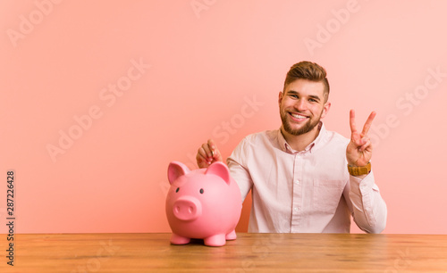 Young caucasian man sitting with a piggy bank showing number two with fingers Wallpaper Mural