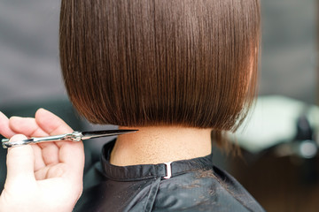 close up hands of professional hair stylist makes short hair with scissors