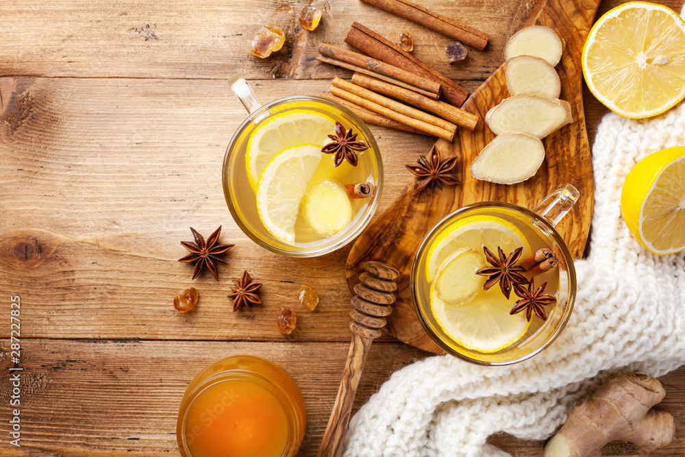 Fototapeta Healing ginger tea in two glass mug in scarf with lemon, honey and spices. Autumn hot drink on rustic wooden table top view.