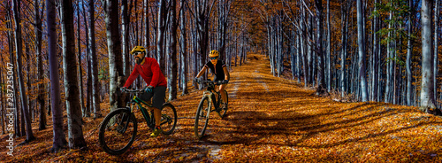 Cycling, mountain biker couple on cycle trail in autumn forest Wallpaper Mural