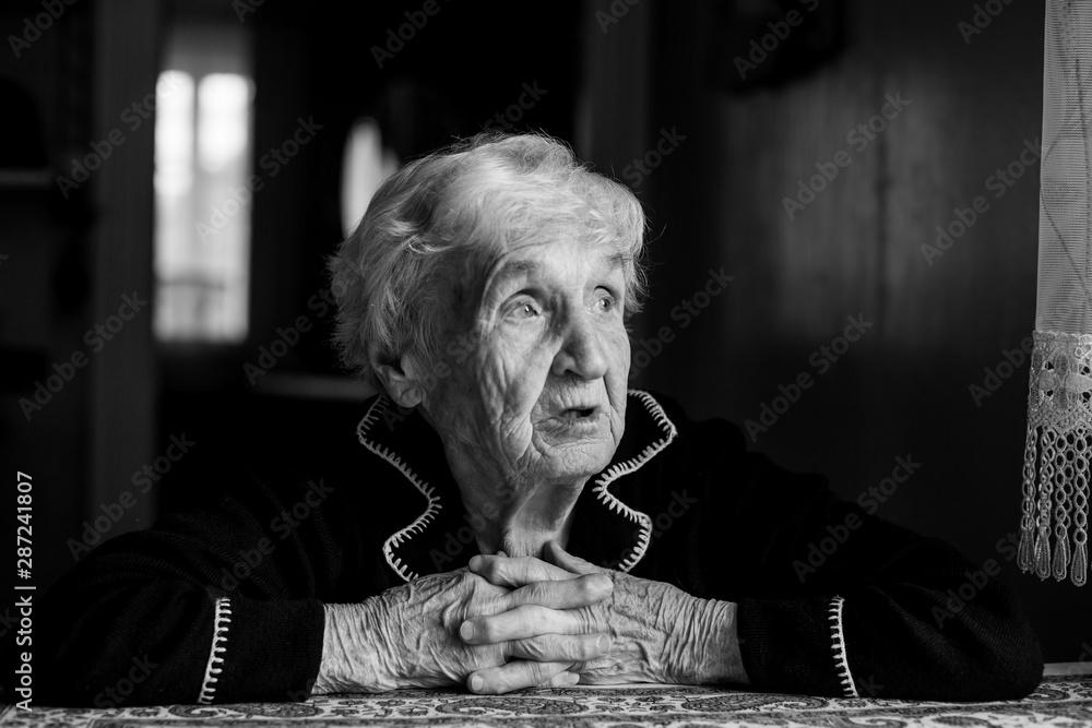 Fototapeta Old lady in a dark key portrait. Black-and-white photo.
