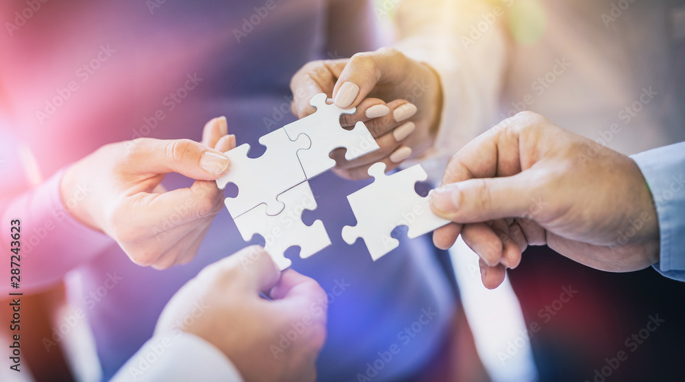 A group of business people assembling jigsaw puzzle.