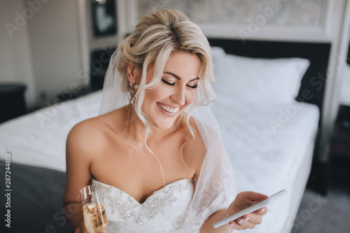 A beautiful, smiling blonde bride in a white dress is sitting on the bed and looking at the phone, reading a message and drinking champagne Fotobehang