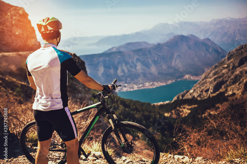Athletic sportsman cyclist standing with bike enjoying beautiful view Canvas Print