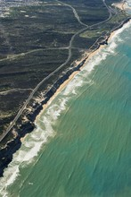 Aerial Vertical Shot Of A Road In The Middle Of Grassy Fields Near A Beach Shore
