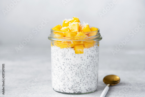 Obraz Chia seed pudding with mango and coconut in glass jar on bright grey concrete background. Healthy food, clean eating dieting vegan lifestyle concept - fototapety do salonu