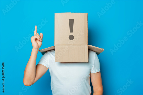 Young man in a white T-shirt with a cardboard box on his head ma фототапет