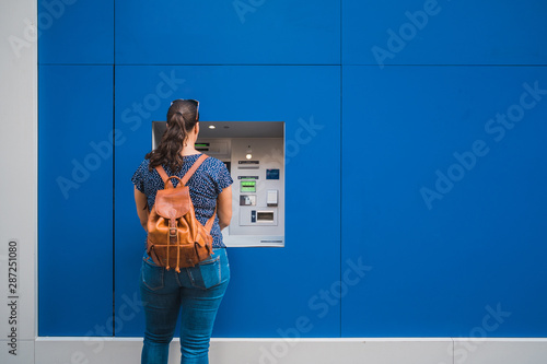 Fototapeta Young beautiful woman inserting credit card and withdrawing money from ATM machine. Young woman taking money form automated teller machine obraz