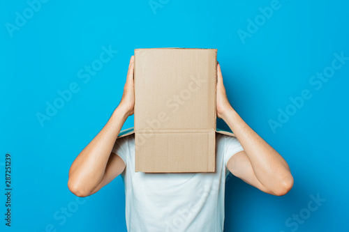 Young man in a white T-shirt with a cardboard box on his head makes a gesture wi фототапет