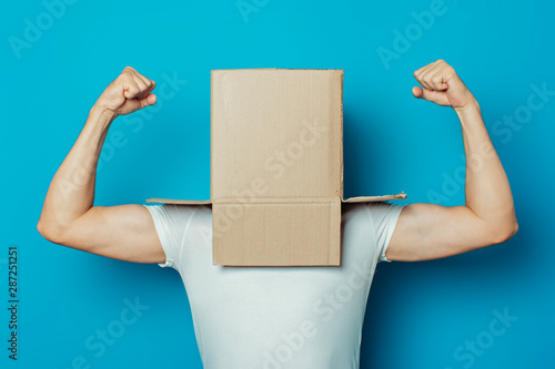 Young man in a white T-shirt with a cardboard box on his head on a blue background фототапет