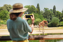 Happy Asian Zoology Student Girl Taking Photo On Smartphone While Giraffe Drinking From Lake