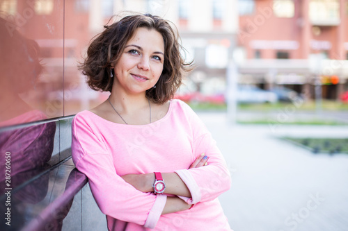 Young Caucasian woman with crossed arms and slight smile leaned against the wall Wallpaper Mural