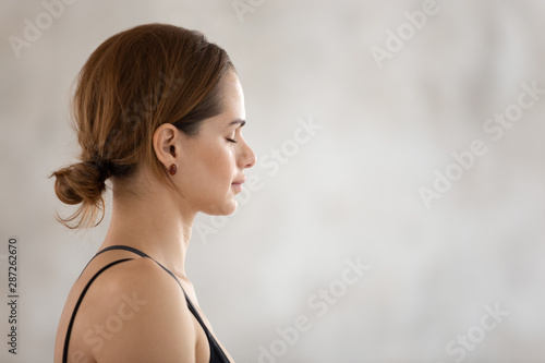 Foto Beautiful woman with closed eyes practicing yoga, meditating, profile view
