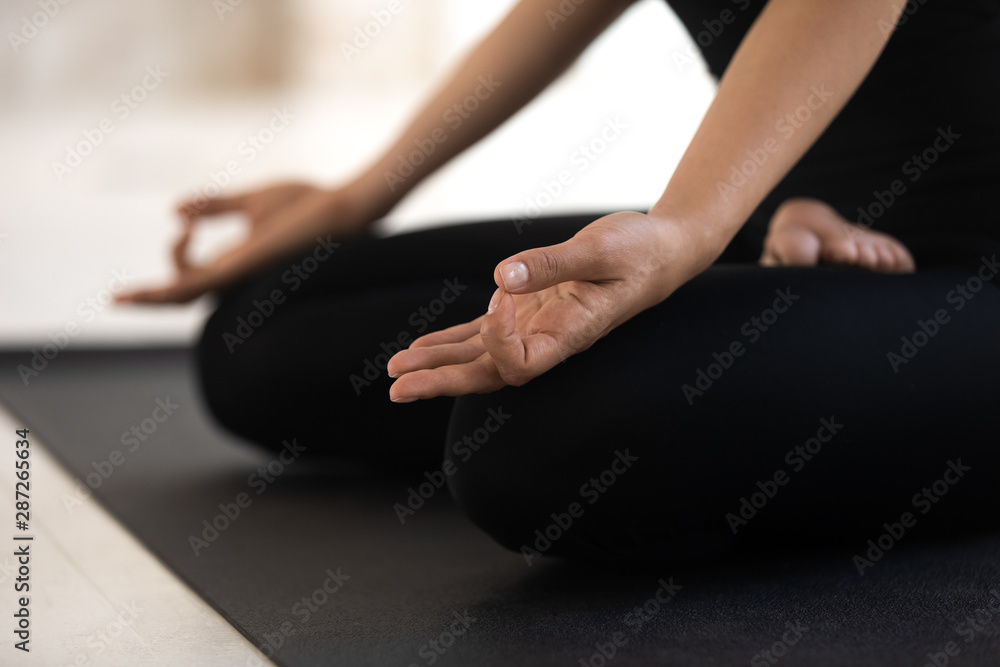 Fototapety, obrazy: Woman sitting in lotus pose close up, practicing yoga, Padmasana exercise