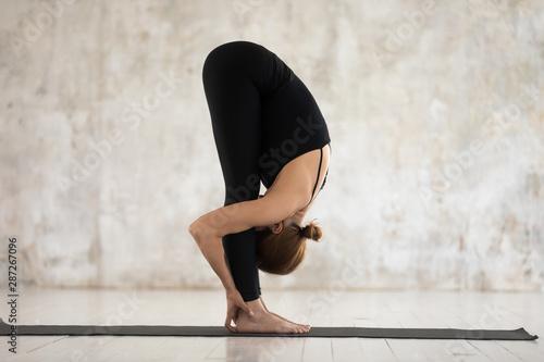 Foto Beautiful woman practicing yoga, uttanasana, standing forward bend
