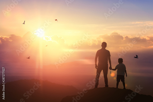 Father and son holding hand in hand on background sunset. Father holiday - 287277027