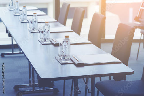 Fototapeta Plastic water bottles, Drinking glasses with pencil and white papers setup on the table prepared for seminar or business meeting in the hotel conference room obraz