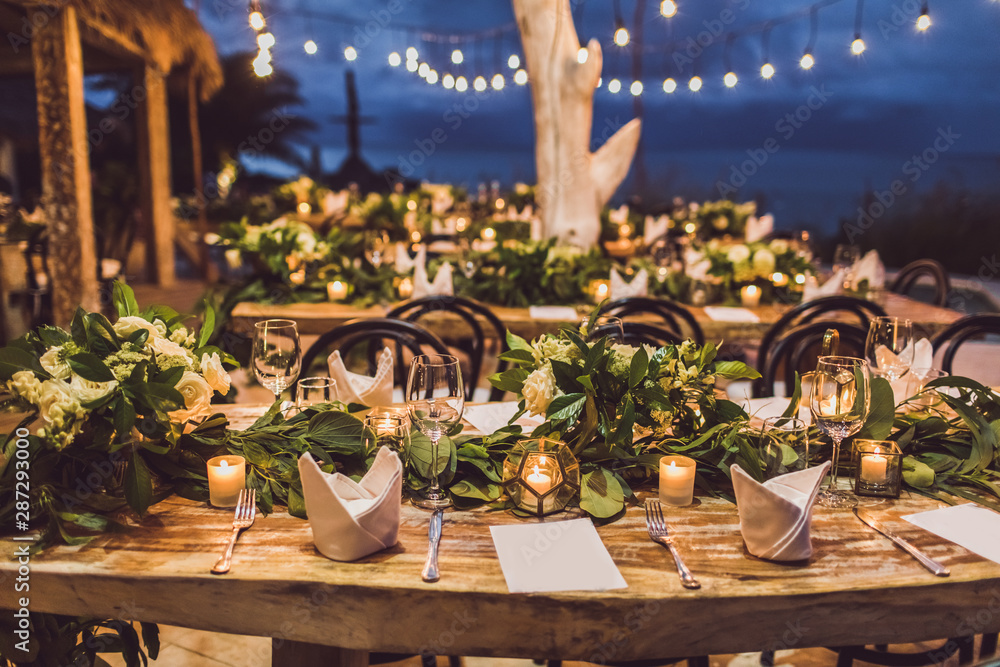 Fototapeta Table setting at night wedding ceremony. Decoration with fresh flowers, candles, light bulbs, garlands. Vintage style.