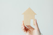 Woman hand holding wood house model on white background. Buying a new real estate as a gift to family concept,