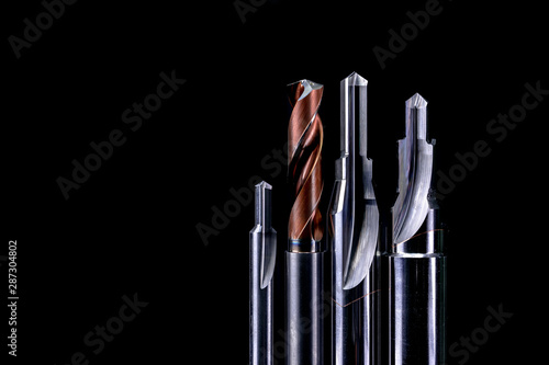 Photo sur Toile Spirale Special tools isolated on dark background. Made to order special tools. Coated step drill and reamer detail. HSS cemented carbide. Carbide cutting tool for industrial applications. Engineering tools.