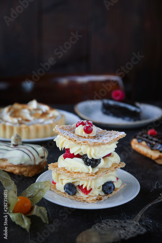 Fotografia Tea and sweets on a dark background, Mille-feuille, Eclairs, Tart, Decorative wi