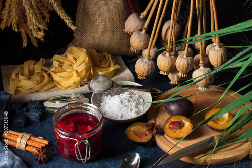 Sweet pasta dessert, noodles with poppy seeds, plum compote from fresh plums, dark background, blue table decorated with fresh flowers Tapéta, Fotótapéta