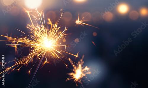 Obraz Glittering burning sparkler against blurred bokeh light background - fototapety do salonu