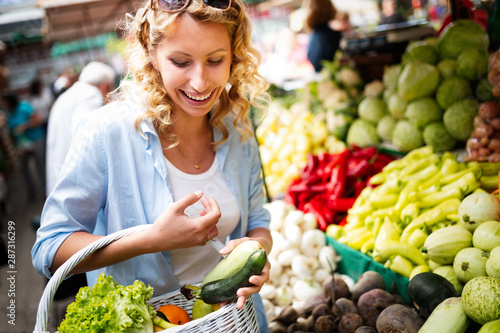 Young woman buying vegetable on stall at the market Wallpaper Mural