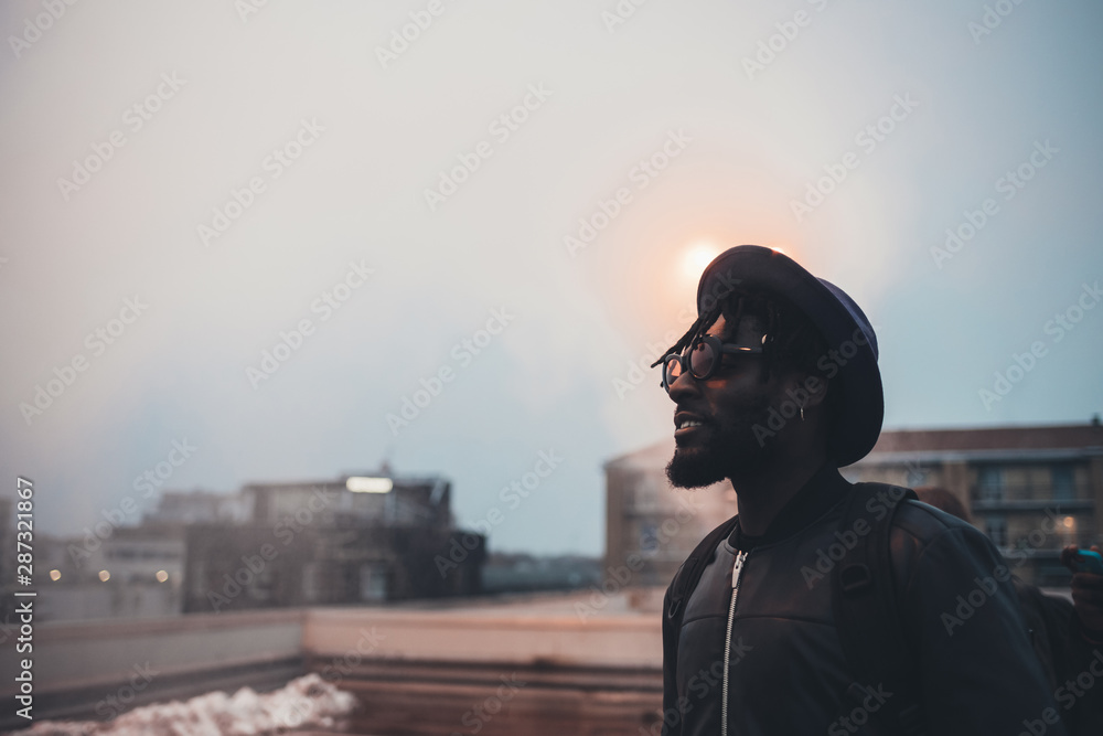 Fototapeta portrait of young african man standing on terrace and looking horizon