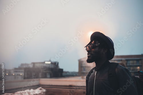 obraz dibond portrait of young african man standing on terrace and looking horizon