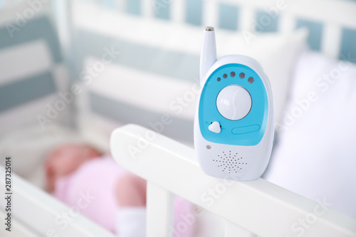 Radio nanny on bed with sleeping baby Fototapet