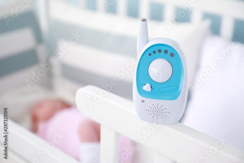 Billede på lærred Radio nanny on bed with sleeping baby