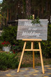 Wooden board with the inscription Welcome to our wedding decorated with green branches. Wedding ceremony.