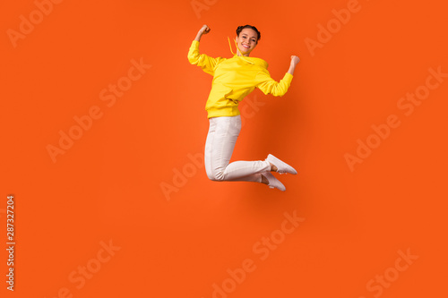 Full body photo of lovely teen raising fists smiling isolated over orange background