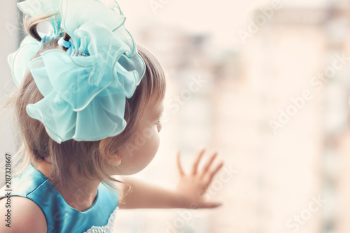 Fotografia  little girl of three years with blue bows and dress looks and touches the window