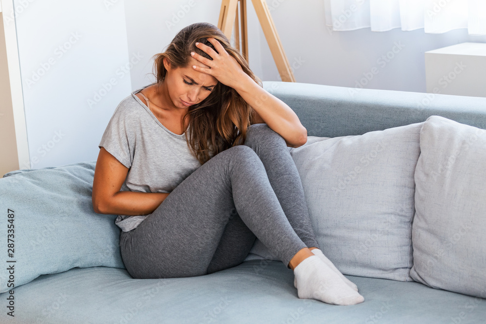 Fototapety, obrazy: View of young woman suffering from stomachache on sofa at home. Woman sitting on bed and having stomach ache. Young woman suffering from abdominal pain while sitting on sofa at home