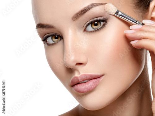 Canvas Print Beautiful woman applying eyeshadow use makeup brush