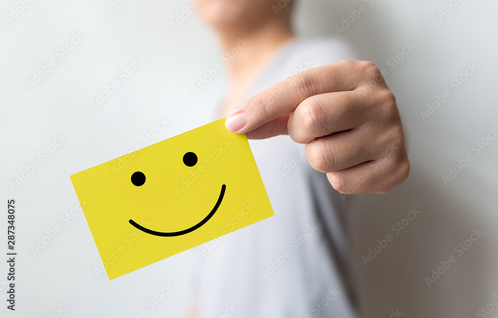 Fototapeta Customer service experience and business satisfaction survey. Man holding yellow card with smiley face