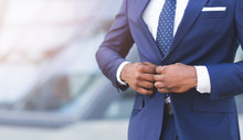 Unrecognizable Black Businessman Fastening Jacket In Urban Area