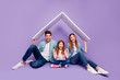 canvas print picture - Portrait of three family members sitting floor under new roof wear casual clothes isolated purple background