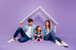 canvas print picture - Family portrait of three members sitting floor under new roof wear casual clothes isolated purple background