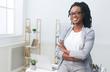 Leinwandbild Motiv Happy African American Businesswoman Sitting On Office Table Indoor