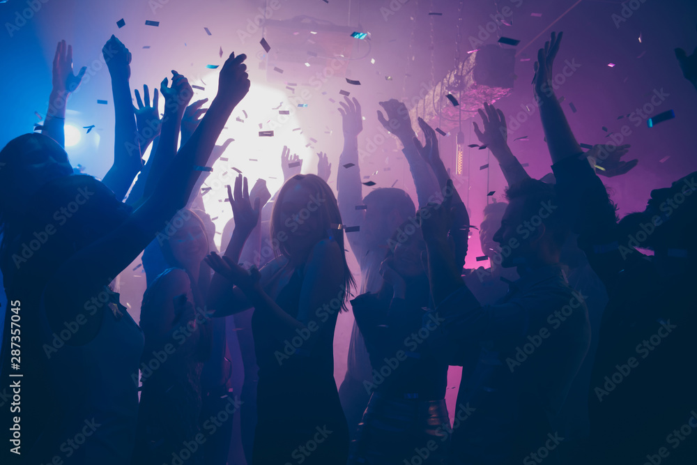 Fototapeta Close up photo of many party people dancing purple lights confetti flying everywhere nightclub event hands raised up wear shiny clothes