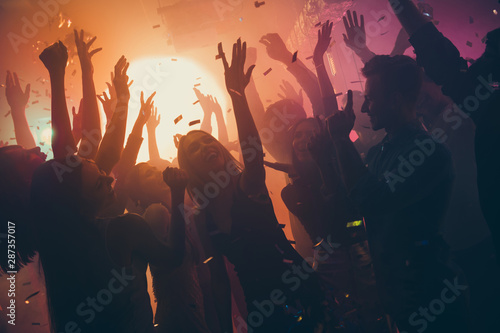 Obraz Photo of many party people buddies dancing yellow lights confetti flying everywhere nightclub event hands raised up wear shiny clothes - fototapety do salonu